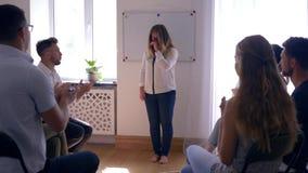 Nieszczęśliwa dziewczyna dzieli jej problemy i zaczyna płakać podczas doradzać terapię, grupa ludzi oklaskuje i poparcia zbiory