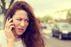 Nieszczęśliwa gniewna młoda kobieta opowiada na telefonie komórkowym patrzeje udaremniający Obrazy Royalty Free