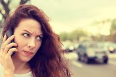 Nieszczęśliwa gniewna młoda kobieta opowiada na telefonie komórkowym patrzeje udaremniający Zdjęcia Stock