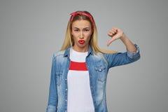 Nieszczęśliwa i uwłaczająca młoda kobieta z długim blondynem pokazuje znaka kciuka puszek Ona ` s nieszczęśliwy i wzburzony Zdjęcia Stock