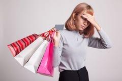 Nieszczęśliwa młoda Azjatycka kobieta z torba na zakupy i kredytową kartą Fotografia Stock