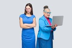 Nieszczęśliwa młoda kobieta stoi blisko szczęście starej kobiety pracy com zdjęcia stock