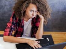Nieszczęśliwa nastoletnia dziewczyna używa laptop zdjęcie stock