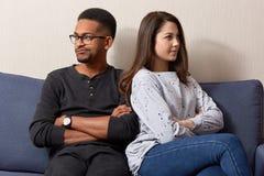 Nieszczęśliwa para różna rasa siedzi z powrotem, no mówić do siebie po tym jak bełt lub spór źle zrozumieć, utrzymanie ręki krzyż fotografia stock