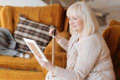 Nieszczęśliwa starsza kobieta trzyma fotografię fotografia stock