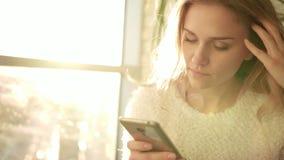 Nieszczęśliwej kobiety texting wiadomość na wiszącej ozdobie Dokuczająca kobieta z smartphone zbiory