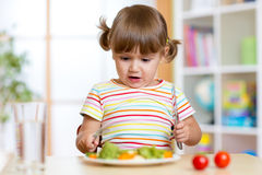 Nieszczęśliwy dziecka obsiadanie przy śniadaniem i niepewnością Obrazy Stock