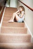 Nieszczęśliwy dziewczyny obsiadanie Na schodkach W Domu Obraz Royalty Free