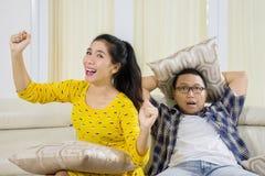 Nieszczęśliwy mąż ogląda film z jego żoną Zdjęcia Stock