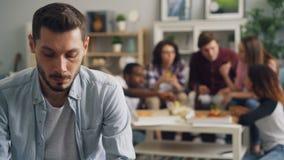 Nieszczęśliwy mężczyzny siedzieć samotny podczas gdy młodzi ludzie świętuje wakacje w tle zbiory wideo