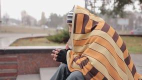 Nieszczęśliwy męski półdupek siedzi samotnie w zimnej ulicie, grżący z kawą i koc zdjęcie wideo