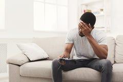 Nieszczęśliwy młody człowiek bawić się wideo gry w domu i gubi obraz royalty free