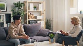 Nieszczęśliwy nastolatek ma rozmowę z doświadczonym terapeutą w biurze