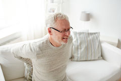 Nieszczęśliwy starszego mężczyzna cierpienie od backache w domu Fotografia Stock