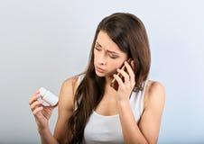 Nieszczęśliwy zmieszany młodej kobiety mienie, patrzeć na pastylki butelce w ręce i wzywać telefon komórkowego pytać lekarkę zdjęcia stock