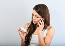 Nieszczęśliwy zmieszany młodej kobiety mienie, patrzeć na pastylki butelce w ręce i wzywać telefon komórkowego pytać lekarkę obraz royalty free