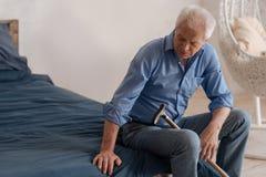 Nieszczęśliwy zwarzony mężczyzna obsiadanie na łóżku fotografia stock