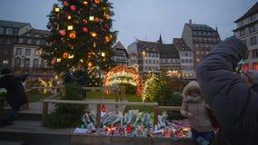Nieszezególni ludzie fotografują na smartphone blisko choinki, kwiaty i świeczki ku pamięci ofiar zbiory wideo