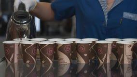 Niet erkende installatiearbeider in blauwe eenvormige proefwerkkoppen door hete koffie te gieten stock video