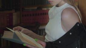Niet erkende jonge vrouw die een boek in een bibliotheek lezen die zich voor boekenrek bevinden Vrije tijd van slimme aantrekkeli stock footage