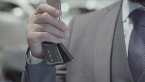 Niet erkende succesvolle bedrijfsmens in een pak die de sleutel van een luxeauto tonen die de camera onderzoeken Auto stock video