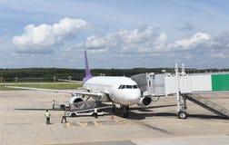 Niet geïdentificeerd die mensen en vliegtuig aan jetway worden aangesloten stock afbeelding