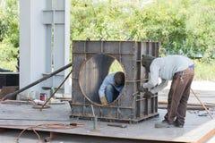 Niet geïdentificeerde arbeider die door grote metaaldoos te lassen werken stock foto