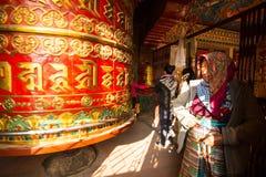Niet geïdentificeerde bedevaart die dichtbij Groot Tibetaans Boeddhistisch gebedwiel spinnen in Boudhanath Stupa Stock Afbeeldingen