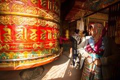 Niet geïdentificeerde bedevaart die dichtbij Groot Tibetaans Boeddhistisch gebedwiel spinnen in Boudhanath Stupa, 20 Dec, 2013 in Stock Foto's