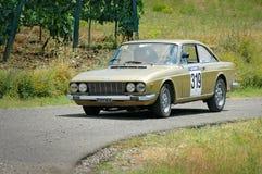 Niet geïdentificeerde bestuurders op gouden uitstekend Fiat 124 coupéraceauto Stock Foto's