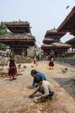 Niet geïdentificeerde jonge geitjes die duiven met droog graan voeden bij Durbar-Vierkant in Bhaktapur, Katmandu, Nepal, na belan Royalty-vrije Stock Foto
