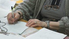 Niet geïdentificeerde leraars chechs taak in notitieboekje stock video