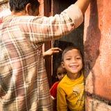 Niet geïdentificeerde lokale kinderen dichtbij hun huizen op een slecht gebied van de stad stock afbeelding