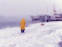 Niet geïdentificeerde mens die dichtbij Karakoy-pijler op een sneeuwdag lopen stock afbeelding