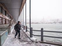 Niet geïdentificeerde mens die onder de galatabrug lopen op een sneeuwdag in de winter royalty-vrije stock foto's