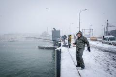 Niet geïdentificeerde mens die op de galatabrug vissen op een sneeuwdag in de winter stock fotografie