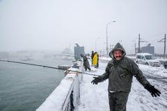 Niet geïdentificeerde mens die op de galatabrug vissen op een sneeuwdag in de winter royalty-vrije stock afbeelding