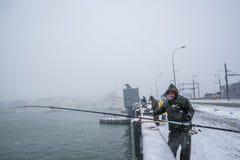 Niet geïdentificeerde mens die op de galatabrug vissen op een sneeuwdag in de winter Stock Afbeelding