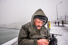 Niet geïdentificeerde mens die op de galatabrug vissen op een sneeuwdag in de winter Stock Foto's
