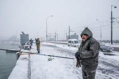 Niet geïdentificeerde mens die op de galatabrug vissen op een sneeuwdag in de winter Stock Foto