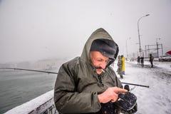 Niet geïdentificeerde mens die op de galatabrug vissen op een sneeuwdag in de winter Royalty-vrije Stock Fotografie