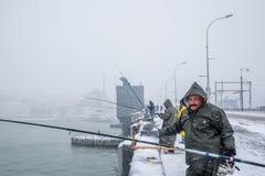 Niet geïdentificeerde mens die op de galatabrug vissen op een sneeuwdag in de winter Royalty-vrije Stock Foto's