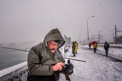 Niet geïdentificeerde mens die op de galatabrug vissen op een sneeuwdag in de winter Royalty-vrije Stock Afbeeldingen