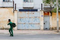 Niet geïdentificeerde mens in het eenvormige lopen onderaan de straat in Azië Royalty-vrije Stock Foto's