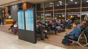 Niet geïdentificeerde mensen die op hun vlucht in Sabiha Gokcen International Airport-ZAAG in Istanboel, Turkije wachten royalty-vrije stock foto