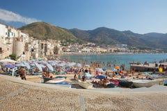 Niet geïdentificeerde mensen op zandig strand in Cefalu, Sicilië, Italië Stock Foto's