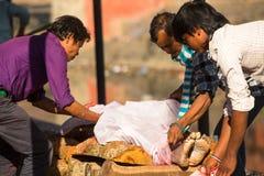Niet geïdentificeerde plaatselijke bevolking tijdens de crematieceremonie langs de heilige Bagmati-Rivier Stock Foto