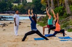 Niet geïdentificeerde volwassenen die aan yoga op het strand deelnemen royalty-vrije stock fotografie