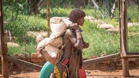 Niet geïdentificeerde vrouw van de stam van de dragende goederen van Hamar in de Omo-Vallei van Ethiopië stock foto