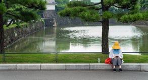 Niet geïdentificeerde vrouwenzitting door de vijver van Keizerpaleis, Tokyo, Japan stock afbeelding